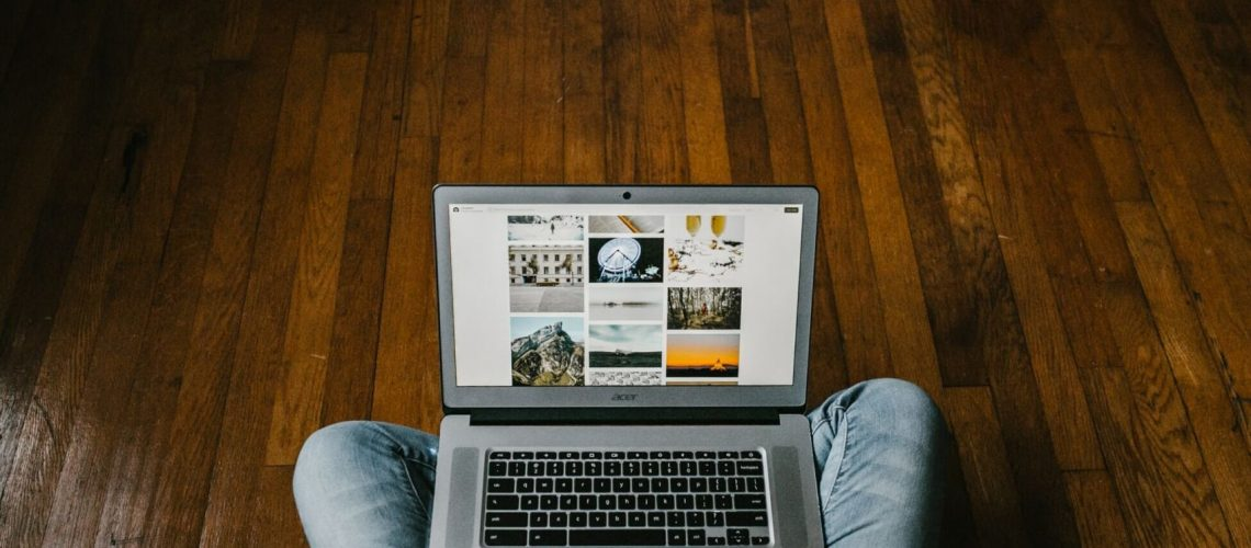 What is Paid Search? Person sitting on Laptop on Wooden Floor